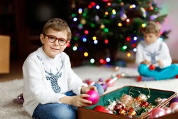 Beautiful kid boy with eye glasses and colorful vintage xmas toys and balls in old suitcase. children decorating Christmas tree
