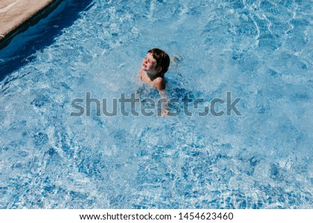 beautiful kid girl at the pool swimming and having fun. fun outdoors. Summertime and lifestyle concept