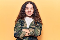 Beautiful kid girl with curly hair wearing camouflage jacket happy face smiling with crossed arms looking at the camera. positive person.