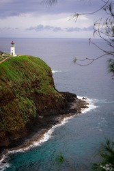 Beautiful Kilauea lighthouse on the coastline of Kauai in Hawaii from a unique overlook above majestic sea with ocean waves bashing against rugged cliffs on an overcast spring day. Calm and tranquil.