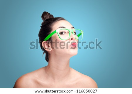 beautiful kissing girl with green eyeglasses on gray background