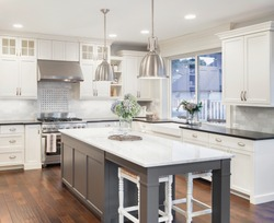beautiful kitchen in luxury home with island, pendant lights, cabinets, and hardwood floors. tile back splash, stainless steel oven,range, and hood compliment the elegant features