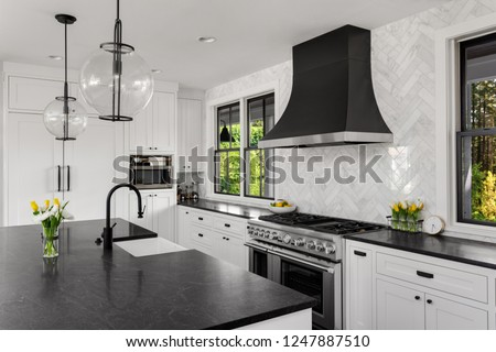 Beautiful Kitchen in New Luxury Home. Features Black Counters and Island, with White Woodwork and Cabinetry. Lights are Turned Off.