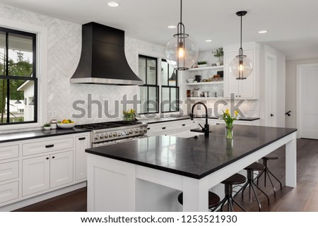 Beautiful Kitchen in New Luxury Home. Features Black Counters and Island, with White Woodwork and Cabinetry. Lights are Turned On.