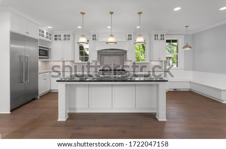 Beautiful kitchen in new luxury home with large island, hardwood floor, stainless steel refrigerator, and pendant lights