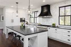 Beautiful Kitchen in New Luxury Home with White Cabinets and Black Accents, including Black Island Countertop. Features Hardwood Floors, Eating Nook, Island with Sink, and Built-In Refrigerator.