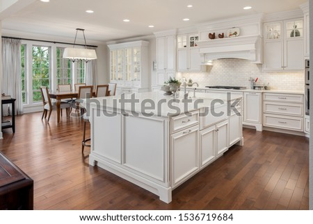 Beautiful kitchen in new traditional style luxury home. Features white island, counters, and cabinetry, and dark hardwood floors. Shows dining area.