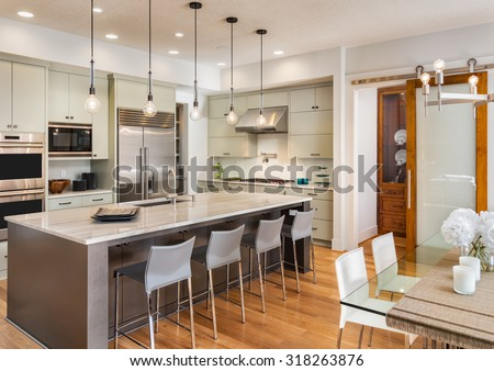 Beautiful Kitchen Interior in New Luxury Home: Kitchen with Island, Sink, Dining Room Table, Stainless Steel Refrigerator, Pendant Lights, Microwave, Oven, Range, and Chairs