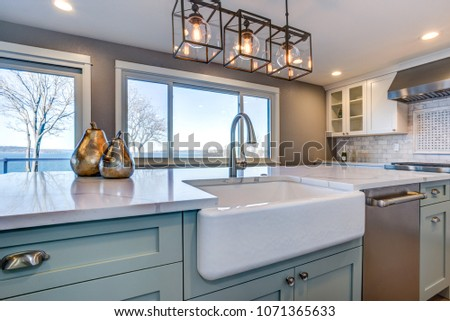 Beautiful kitchen room with green island and farmhouse sink. #1071365633