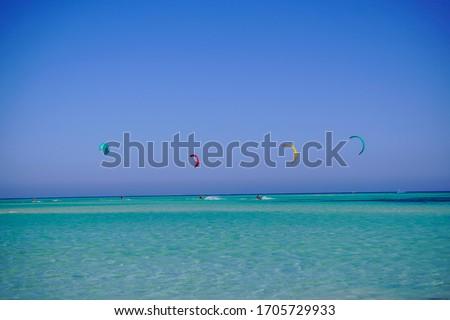 Photo of  Beautiful Kitesurfers riding by a beautiful Tawilla Island, Red Sea - Kitesurfing in Egypt 01