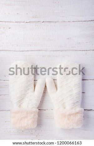 Beautiful knitted warm white mittens on a wooden background #1200066163