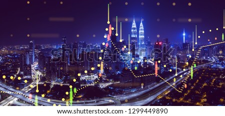 Beautiful Kuala Lumpur skyline at night with financial chart state blend in effect .