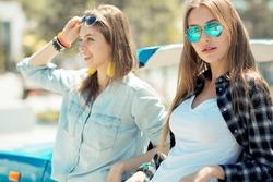 Beautiful ladies in sun glasses posing near vintage car cabriolet