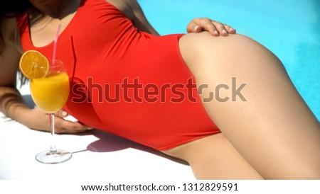 Beautiful lady enjoying cold summer cocktail, lying near swimming pool, suntan #1312829591