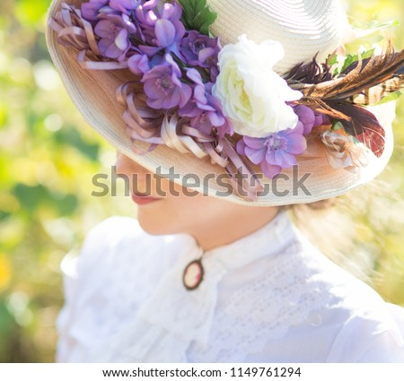 beautiful lady in a hat with flowers in a historic dress smiling