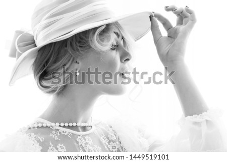 Beautiful lady in elegant hat on a white background. Black and white photography #1449519101