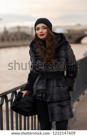 Beautiful lady in gray fur coat and cashmere cap at river embankment on a cold day. Fall winter fashion look.
