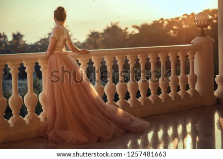 Beautiful lady in luxurious ballroom dress with tulle skirt and lacy top standing on the large balcony looking away at sunset. Back view. Text space