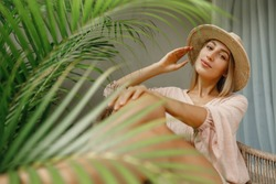 Beautiful lady in straw hat  in greenery looking at the camera, sitting on the chair on terrace at home. Portrait of a girl in a straw hat close-up