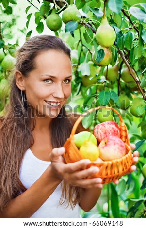 Beautiful lady in the garden with apples and pears in the crib