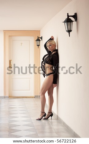 beautiful lady in underwear in front of hotel room doors number seven