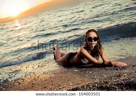 Beautiful lady laying at the beach during summer sunset.