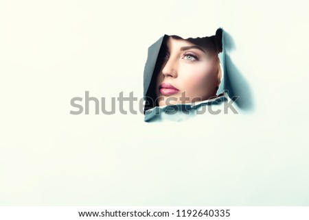 Beautiful lady looking from behind background. Beauty, make up.