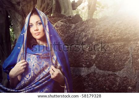 Beautiful lady outdoors in elegant sari near the old stony wall. Horizontal portrait
