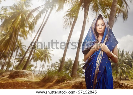 Beautiful lady outdoors in stylish sari standing in the wild jungle. Artistic colors added