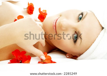 beautiful lady with red flower petals in spa