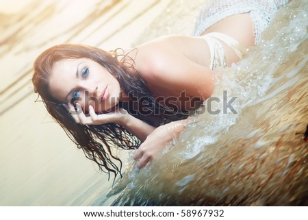Beautiful lady with wet hairs laying on the water during vacation at the tropical beach