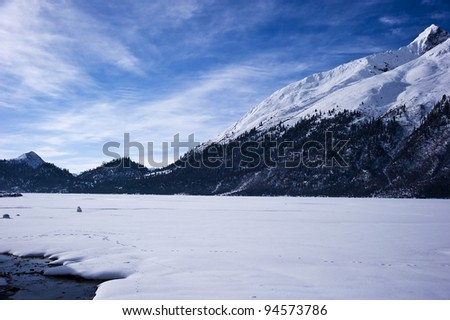 beautiful lake covered by heavy snow  in tibet with blue sky and wonderful white cloud