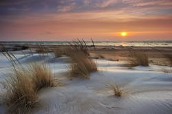 Beautiful Lake Huron Sunrise, Tawas Point State Park, Michigan USA Snow and ice mix with the drifting sand making this a pretty winter scene.