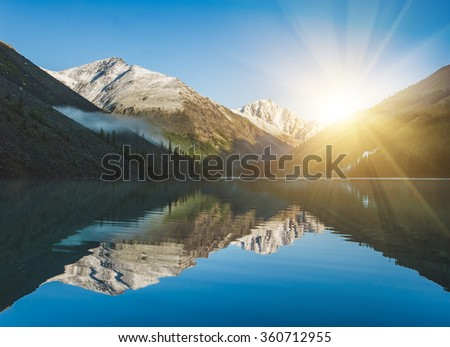 Shutterstock Beautiful lake in Altai. Sunrise and mountains reflected in the water