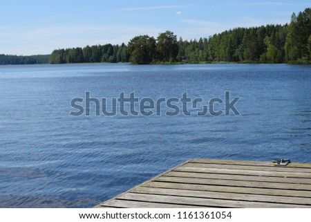 Beautiful lake in Savonia, Finland and part of wooden pier. #1161361054