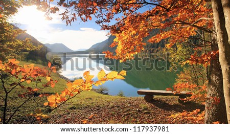 beautiful lake view in autumn, with a wooden bench - stock photo