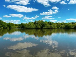 Beautiful lake view with blue sky reflection on water, Epping Forest Connaught Water , north London, England.