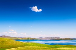 Beautiful lake with green hills and the blue sky with white clouds. Spring nature landscape. South Ural, Bashkortostan Republic, Russia.