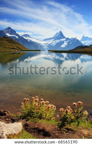 Beautiful lake with swiss mountain reflection, snow, and highest summits. Switzerland - Grindelwald