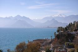 Beautiful landscape against the Mediterranean Sea shore of Antalya Turkey, taurus Mountains with snowy peaks on blue sky.