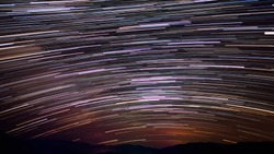 Beautiful landscape backdrop purple crimson starry sky with bright stars stripes at long exposure