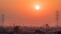 Beautiful landscape before sunset with giant sun on the city of Bangkok, Thailand, city building and high voltage power transmission tower background, High voltage power tower, electricity pylon.