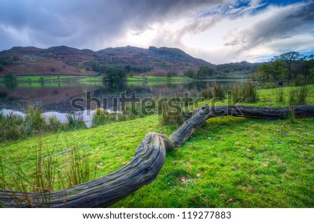 Beautiful Landscape image of Rydal Water in Lake District, a National Park in England, during Autumn with blue/grey sky and view of the distant hills