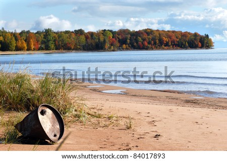 Beautiful landscape is ruined by discarded industrial barrel washed ashore.  Lake Superior in Upper Peninsula, Michigan is alive with Autumn color.