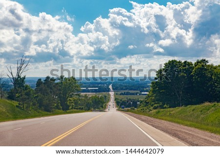 Beautiful landscape midday view of Canadian Ontario country side road with cars traffic during sunny day with white clouds in blue sky. Busy outdoor country village street at summer. stock photo