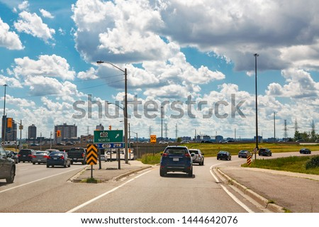 Beautiful landscape midday view of Toronto city highway street with cars traffic during sunny day with white clouds in blue sky. Busy outdoor downtown exit from autobahn motorway road at summer. stock photo