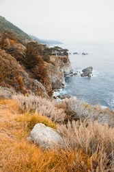 Beautiful landscape near Monterey city in California. Turquoise ocean with big waves and rocky cliffs. Paradise beach of California. Pacific ocean and cliffs with plants.