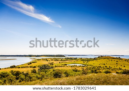 Beautiful landscape of a nature park in Denmark. Lots of islands in the sea with grass lands and clear blue summer sky above. Stockfoto ©