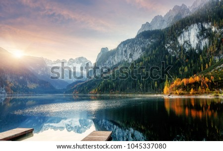 Beautiful Landscape of Alpine Lake with Crystal clear Asure Water and Mountains in Background, Colorful Sky at Sunset reflected in water. Fantastic Nature. Gosausee, Vorderer Lake, Austria. Europe.