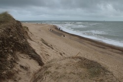 Beautiful landscape of beach at Winterton On Sea in Norfolk East Anglia England UK on stormy skies cold Winter day looking at sandy shore from cliff sand dunes people walking to view seals with pups